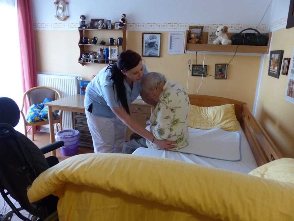 Pflegerin bringt Bewohner des Betreuungszentrums St. Wolfgang zu Bett